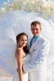 Novia y novio que abrazan delante de arco Imagen de archivo libre de regalías