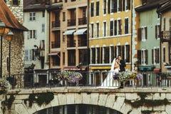 Novia y novio que abrazan en el puente romántico viejo sobre el río y el ch fotos de archivo