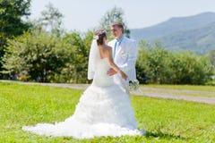 Novia y novio que abrazan en la hierba verde Fotografía de archivo
