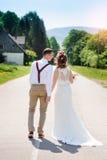 Novia y novio que caminan en el camino Foto de archivo