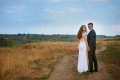 Novia y novio que caminan en el camino en un campo Imagen de archivo
