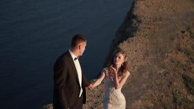 Novia y novio que caminan en la montaña en la puesta del sol almacen de video