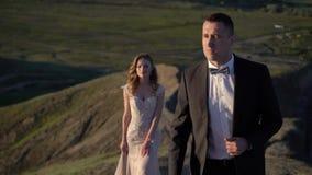 Novia y novio que caminan en la monta?a en la puesta del sol almacen de metraje de vídeo
