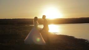 Novia y novio que caminan en la puesta del sol