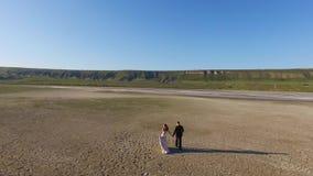 Novia y novio que caminan en la tierra de la textura Lago de sal seco almacen de metraje de vídeo