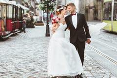 Novia y novio que caminan a través de la calle cobbled Foto de archivo libre de regalías