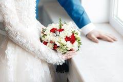 Novia y novio que detienen cierre nupcial del ramo rosas rojas y blancas, fresia, brunia adornadas en la composición Foto de archivo