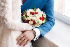 Novia y novio que detienen cierre nupcial del ramo rosas rojas y blancas, fresia, brunia adornadas en la composición Fotos de archivo
