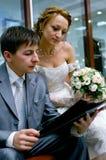 Novia y novio que leen el compartimiento Foto de archivo libre de regalías