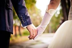 Novia y novio que llevan a cabo las manos Fotos de archivo