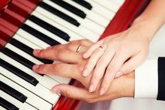 Novia y novio que llevan a cabo las manos con los anillos Foto de archivo libre de regalías