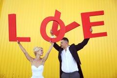 Novia y novio que llevan a cabo letras de amor grandes Imagen de archivo libre de regalías