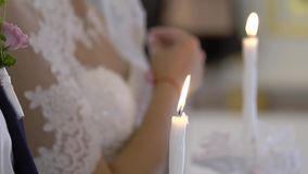 Novia y novio que llevan a cabo velas en iglesia en la ceremonia almacen de video