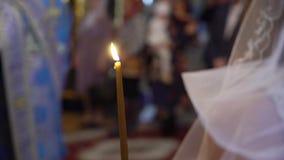 Novia y novio que llevan a cabo velas en iglesia en la ceremonia almacen de metraje de vídeo
