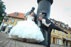 Novia y novio que meten la pata delante de August Senoa Monument Imágenes de archivo libres de regalías