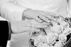 Novia y novio que muestran el anillo de bodas y el ramo imagen de archivo