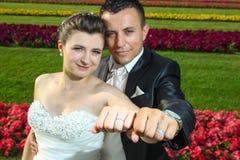 Novia y novio que muestran los anillos de bodas Imagenes de archivo