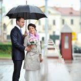 Novia y novio que ocultan de la lluvia en una ciudad vieja Foto de archivo