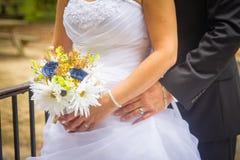 Novia y novio que presentan con las flores Imagen de archivo