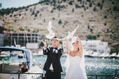 Novia y novio que presentan con las palomas blancas de la boda Fotos de archivo libres de regalías