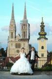 Novia y novio que presentan delante de iglesia Imagen de archivo libre de regalías