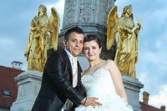 Novia y novio que presentan delante de la fuente Fotos de archivo