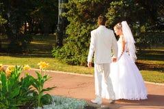 Novia y novio que recorren en parque Foto de archivo libre de regalías
