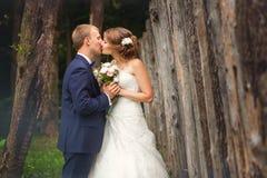 Novia y novio que se besan cerca de la cerca fotografía de archivo