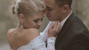 Novia y novio que se besan cerca de las paredes de un castillo