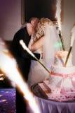 Novia y novio que se besan cerca del pastel de bodas Imagen de archivo