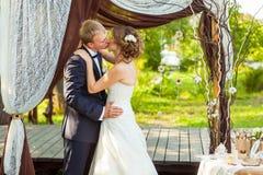 Novia y novio que se besan debajo de arco de la boda imagen de archivo libre de regalías