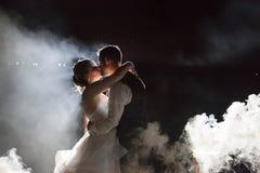 Novia y novio que se besan debajo de la niebla en la noche foto de archivo libre de regalías