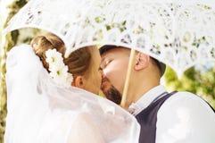 Novia y novio que se besan debajo de un paraguas Fotos de archivo