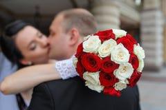 Novia y novio que se besan delante de un ramo de rosas blancas y rojas Imagen de archivo