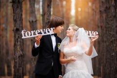 Novia y novio que se besan en el bosque fotos de archivo