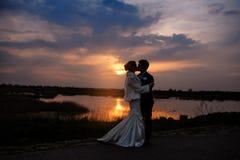 Novia y novio que se besan en la pareja casada romántica hermosa de la puesta del sol fotografía de archivo libre de regalías