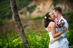 Novia y novio que se besan en las zonas tropicales en un fondo de palmeras imagen de archivo