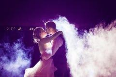 Novia y novio que se besan en niebla con el cielo nocturno púrpura