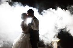 Novia y novio que se besan en niebla en la noche imagen de archivo