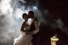 Novia y novio que se besan en niebla en la noche en un muelle foto de archivo