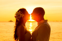Novia y novio que se besan en una playa tropical en la puesta del sol Fotos de archivo