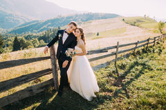 Novia y novio que se colocan de abarcamiento cerca de la cerca de madera en el fondo del camino Imagen de archivo
