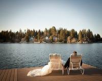 Novia y novio que se relajan en sillas de jardín en el muelle que mira hacia fuera al lago Fotos de archivo