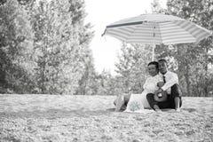 Novia y novio que se sientan en arena en la playa debajo del paraguas imagenes de archivo