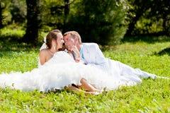 Novia y novio que se sientan en la hierba verde Fotografía de archivo libre de regalías