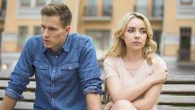Novia y novio que sientan uno al lado del otro enojado, lucha de los pares fotografía de archivo libre de regalías