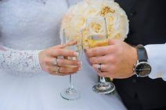 Novia y novio que sostienen los vidrios del champán de la boda Fotografía de archivo