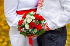 Novia y novio que sostienen un ramo de boda roja Fotos de archivo