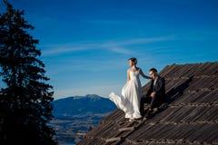 Novia y novio sonrientes encantadores que se colocan en el tejado de la casa de campo Fondo hermoso del paisaje de la montaña Imagen de archivo libre de regalías