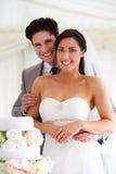 Novia y novio With Wedding Cake en la recepción Fotografía de archivo libre de regalías